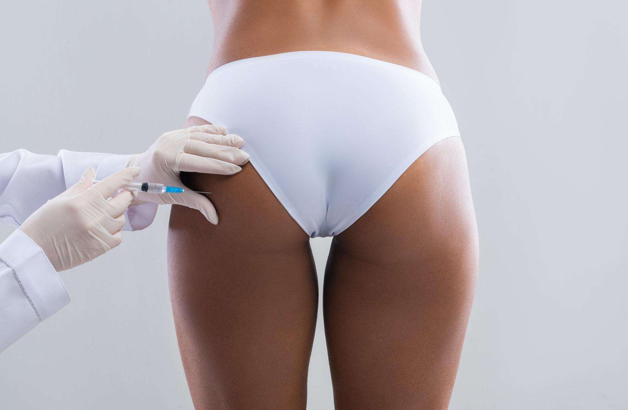 Back view of woman having lipolysis treatment at beauty salon