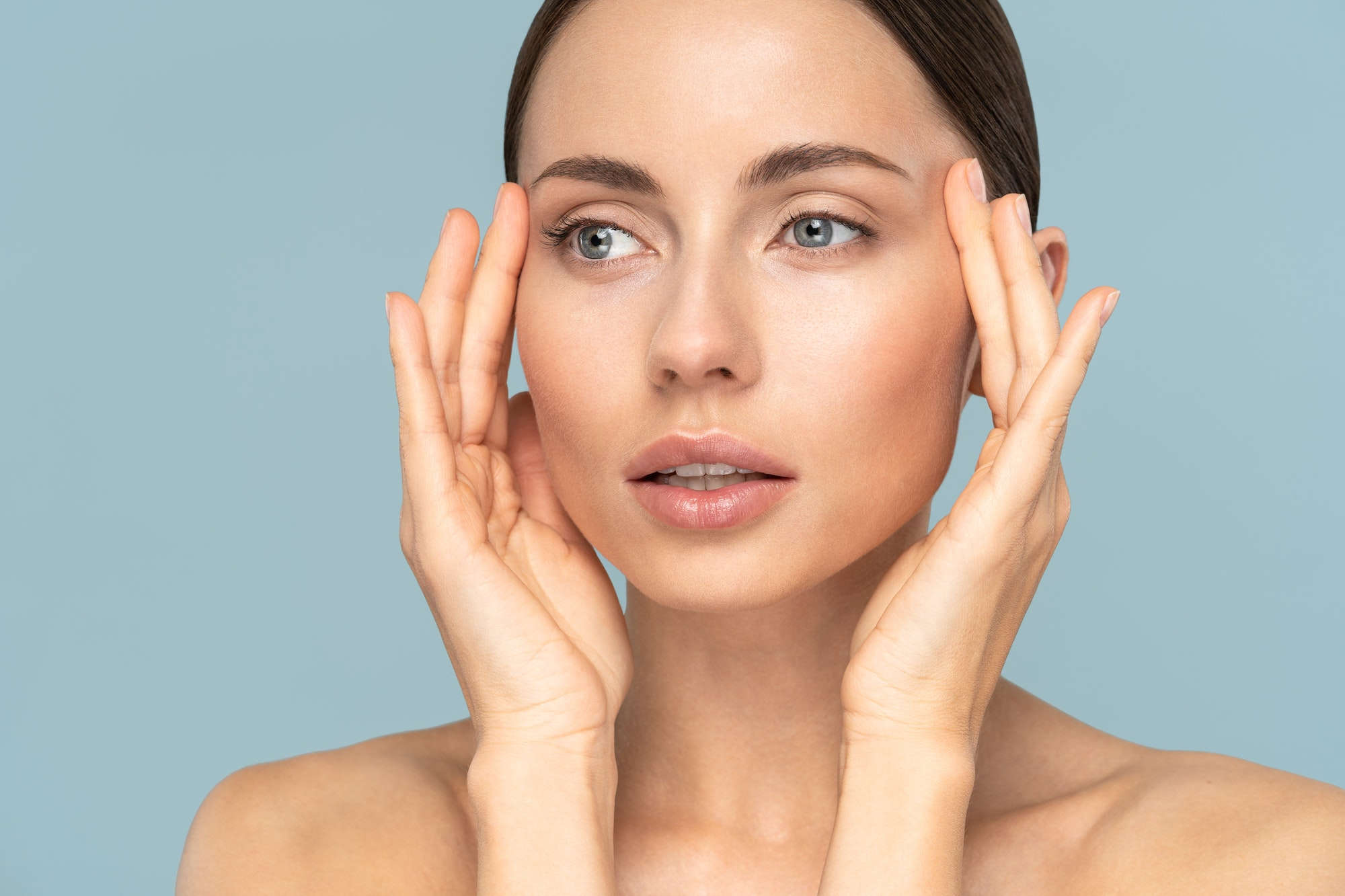 woman with natural makeup, combed hair, touching well-groomed pure skin on face. Beauty, facelift